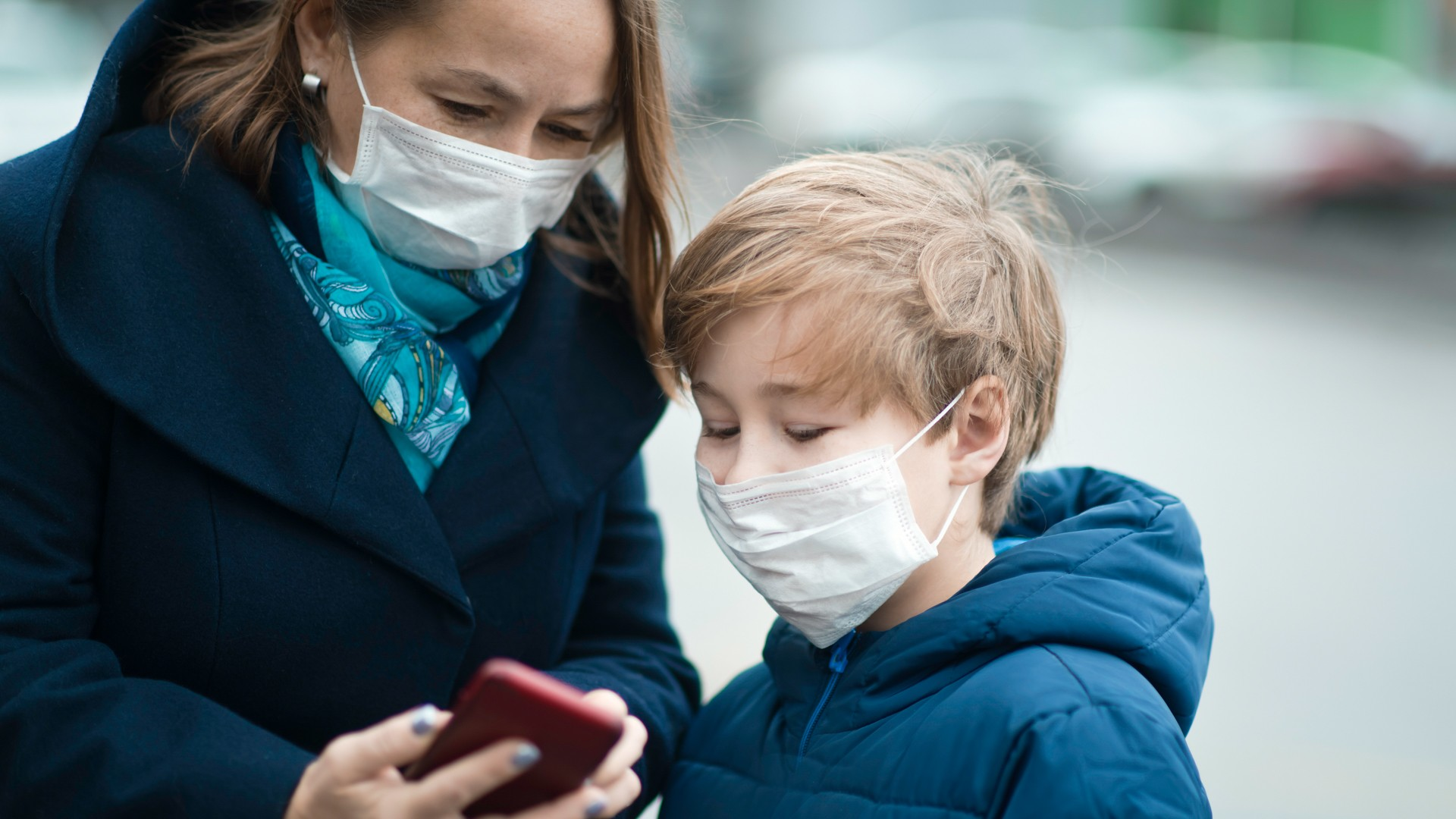 Child and his mother wearing facial mask on a city street.