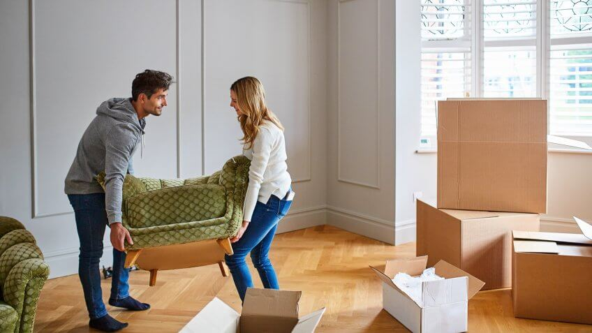 Shot of a happy young couple moving furniture in their new house.