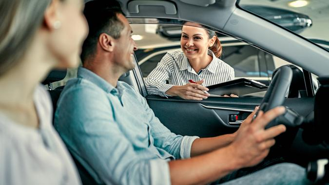Young female consultant and couple buyers sitting in new car signing contract in auto show.