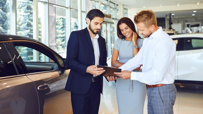 A couple buys a car in a car showroom.