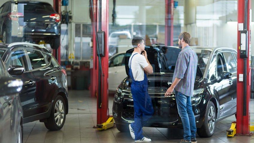 Man having problems with car visiting repair shop.