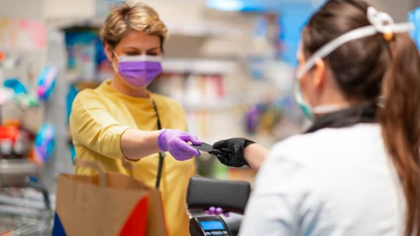 Cashier returning credit card at the cash register to woman with wallet wearing protective face mask and gloves to prevent viruses.