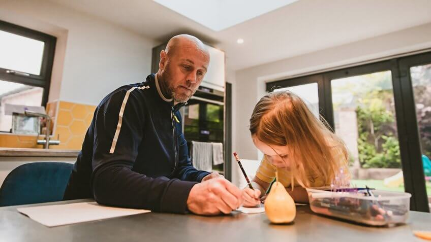Father and his little daughter drawing together in the kitchen.