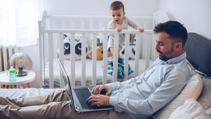 Father finishing up some work on his laptop while his baby son can't wait him to finish up and take him from crib.