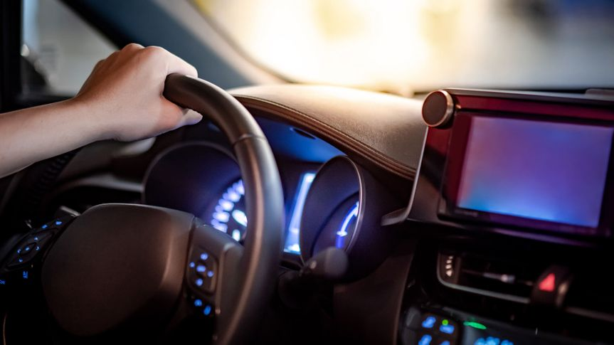Male driver hand holding on steering wheel using digital dashboard monitor for GPS navigation on the car console in modern car.