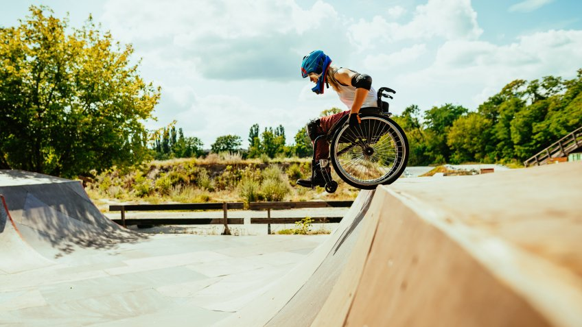 Wheelchair woman performing stunts in skate park - courage and confidence in adaptive sports and hobbies.