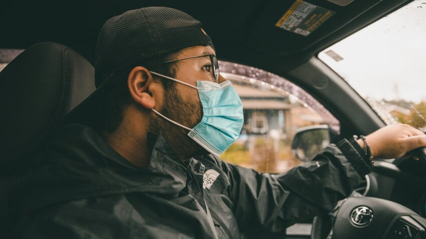 Los Angeles, Ca/USA - April 5, 2020: A millennial wearing a medical face mask while driving.