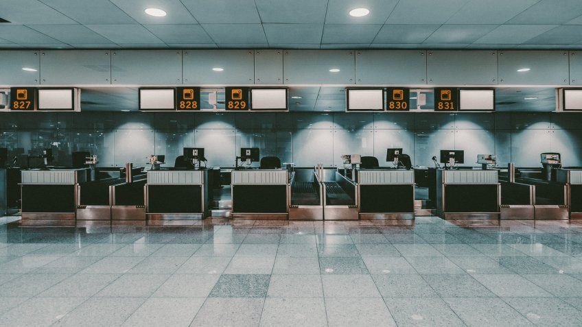 Front view of a check-in area in a modern airport: luggage accept terminals with baggage handling belt conveyor systems, multiple empty white informational LCD screen mockups, indexed check-in desks.