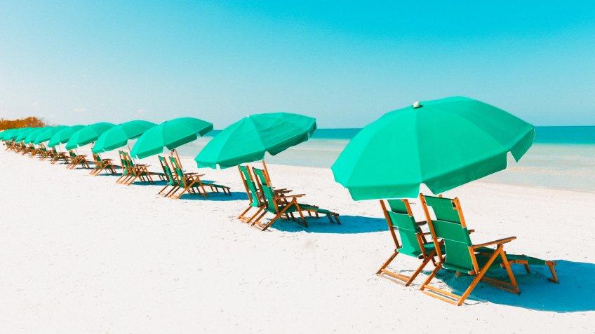 Green beach loungers and umbrellas at white sandy beach.