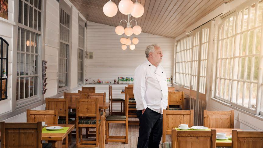 Restaurant owner standing in his empty restaurant.