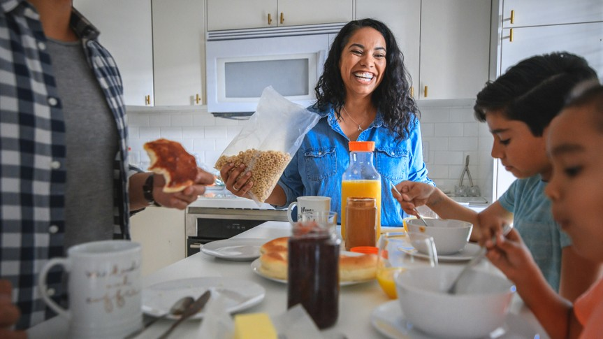 Smiling mid adult woman having breakfast with family.