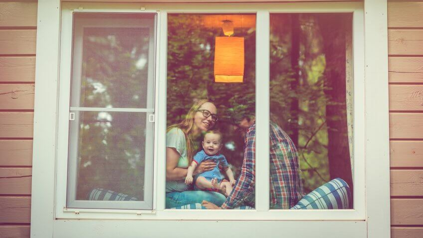 Parents with their baby through a window.