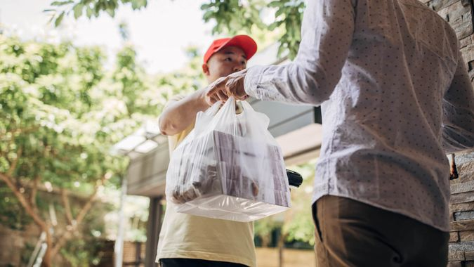 Delivery man bringing food to a customer.