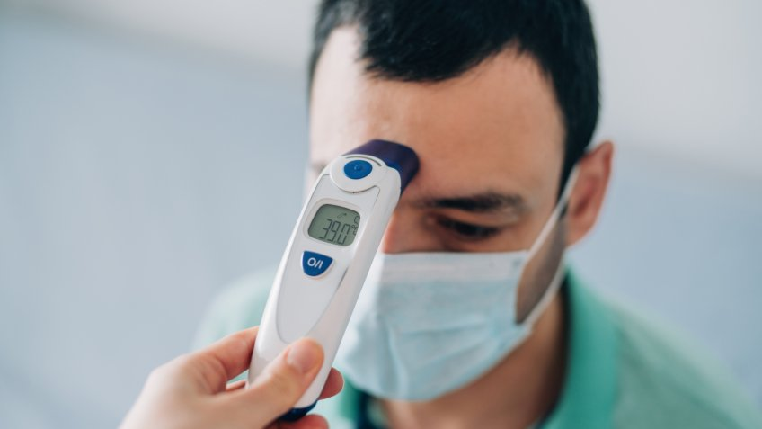 Healthcare worker checking body temperature of a young sick man with contactless digital infrared thermometer.