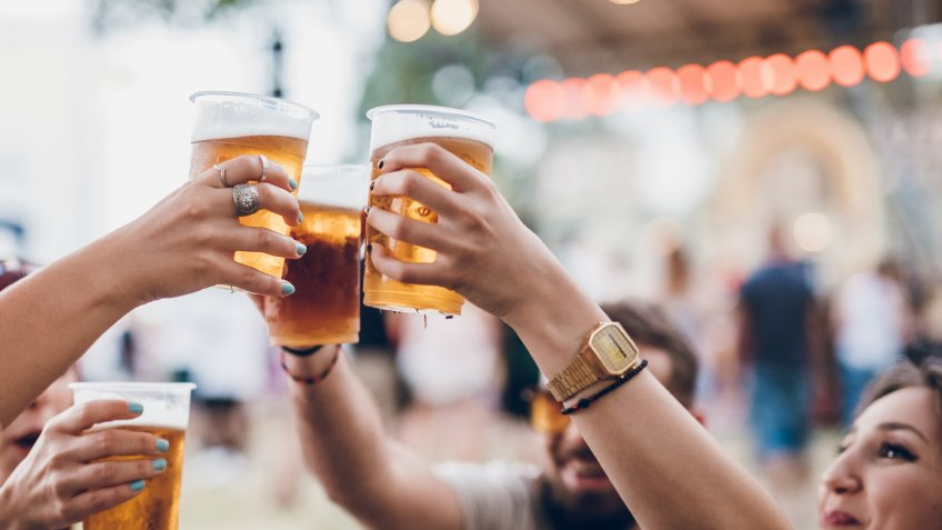 Group of four friends toasting with beer on a music festival.