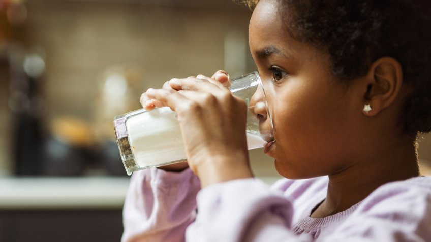 Little African American girl drinking fresh milk from glass at home.