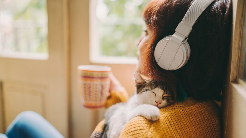 Woman at home listening to music and drinking coffee.
