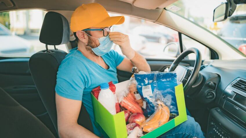 Delivery guy with protective mask and gloves delovering groceries during lockdown and pandemic.