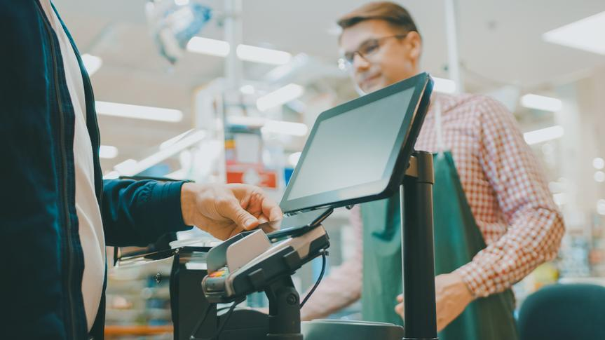 At the Supermarket: Checkout Counter Customer Pays with Smartphone for His Food Items.