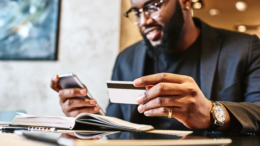 Portrait of African-American male holding cell phone in one hand and credit card in other, making transaction, using mobile banking app during lunch at cafe.