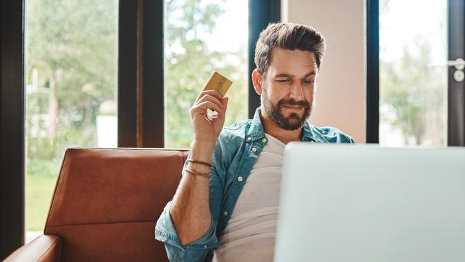 Cropped shot of a handsome young man shopping online while chilling on the sofa at home.
