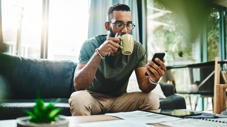 Shot of a young man using a smartphone while going over his finances at home.