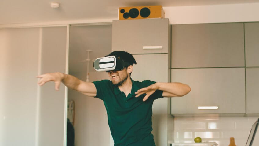 Funny young man in virtual reality 360 headset dancing in the kitchen in the morning while listening to music and have fun at home.