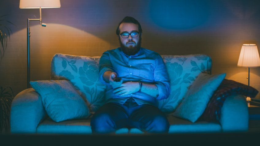 Portrait Shot of a Man Sitting on a Sofa in His Living Room, Watching TV, Changing Channels.