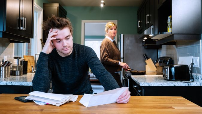 A young man sitting at home stressed by his mounting debts.