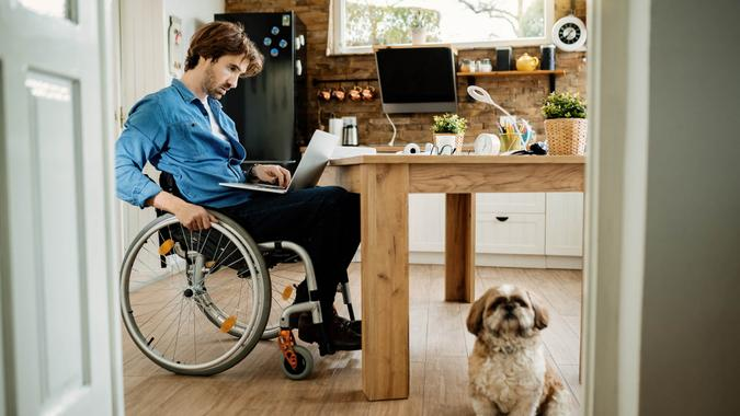 Young disabled freelance worker working on a computer while being with his dog at home.