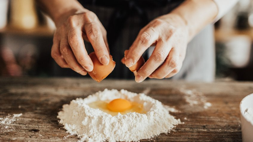 Woman adds an egg to the flour.