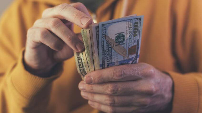 Casual man is counting american dollar banknotes, close up of hands with money.