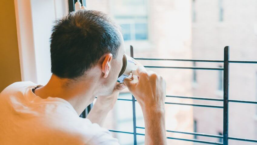 Closeup of young man drinking coffee, tea from cup looking outside of small apartment window in New York City NYC urban Bronx, Brooklyn brick housing, guard rail, security bars.