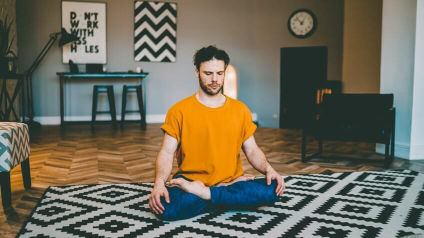 Young man with bristles sitting on yoga mat with eyes closed in center of modern living room and relaxing in easy seat pose.