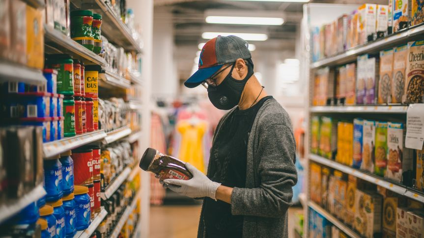 Bethesda, Maryland / USA - April 1, 2020: A man wearing a protective mask and rubber gloves searched for instant coffee at a Target grocery store during the COVID 19 pandemic.