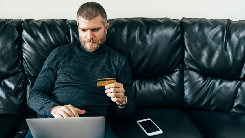 Man at home using credit card for online shopping and payments.