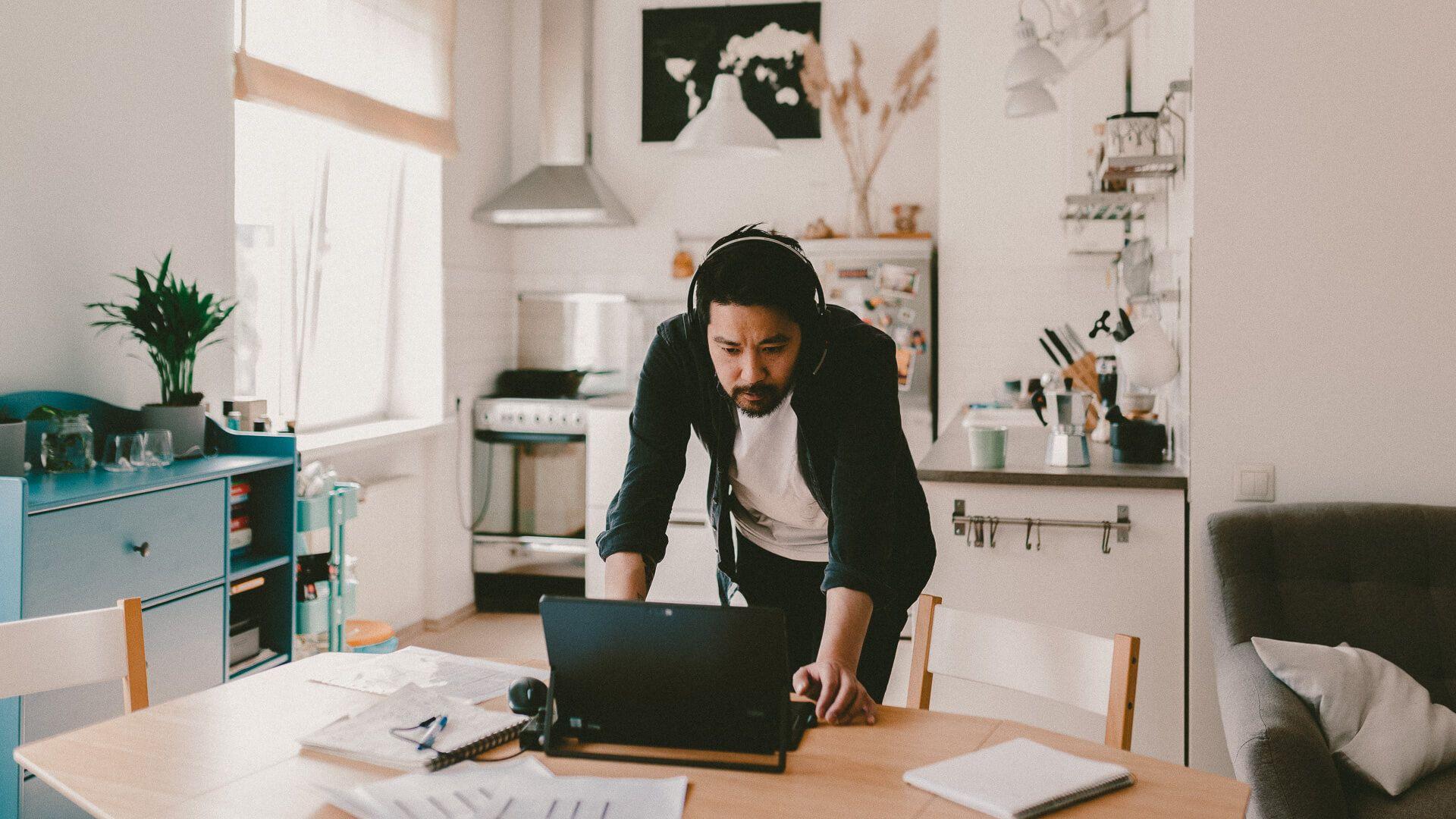 man checking laptop at table