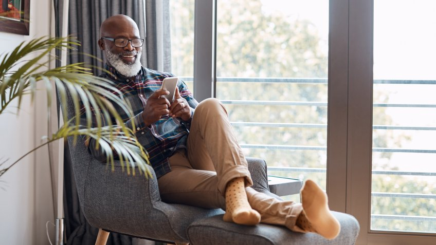 Shot of a mature man using a cellphone while relaxing on a sofa at home.