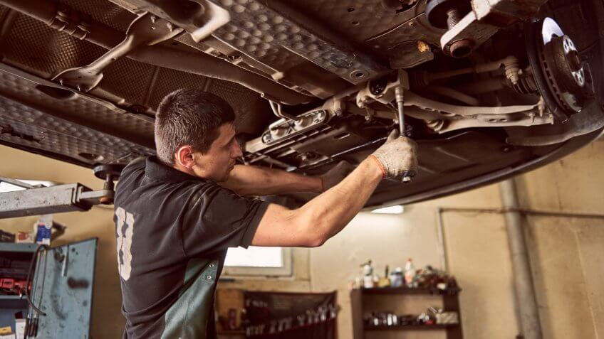Experienced specialist car mechanic standing under lifted car during repair and maintenance process in garage.