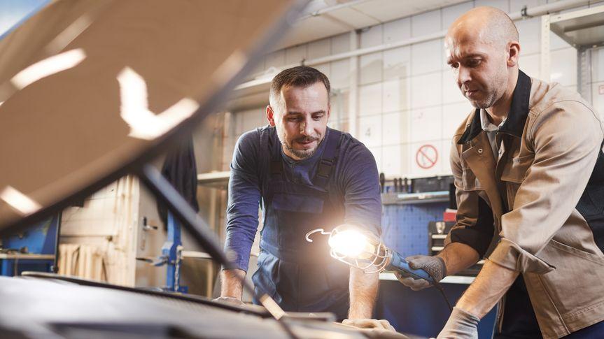 Waist up portrait of two car mechanics looking under hood of car in auto repair workshop, copy space.