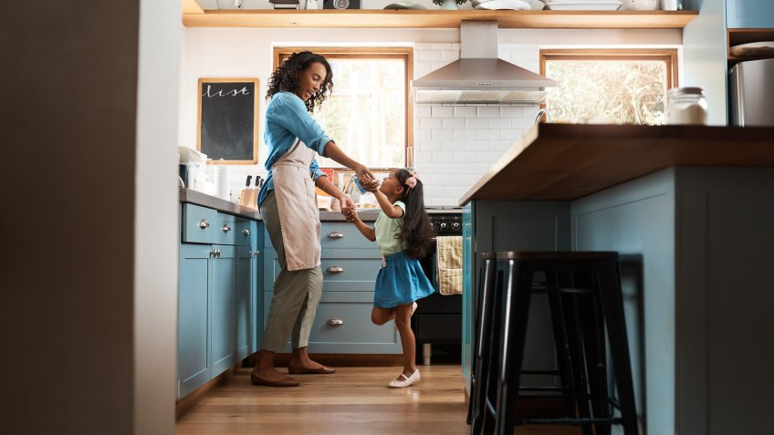 Shot of a young woman dancing with her daughter in the kitchen at home.