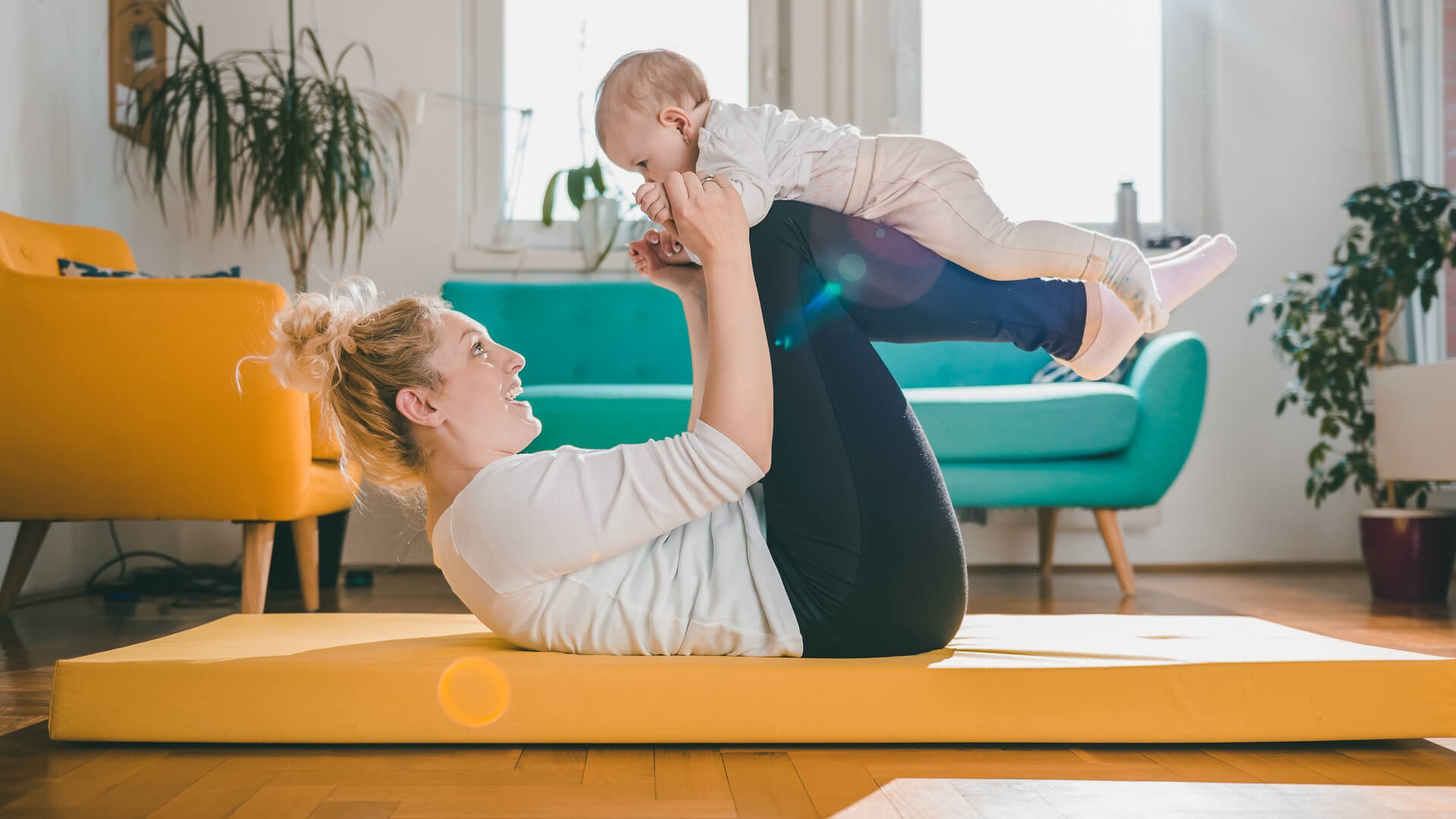 Mother Exercise With Her Baby on yellow mat At Home.
