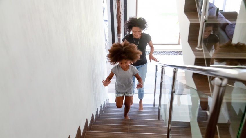 Excited little African American girl run up stairs of new home with young mom, happy black mother and small daughter explore bought house on moving day together, mommy have fun playing with kid.