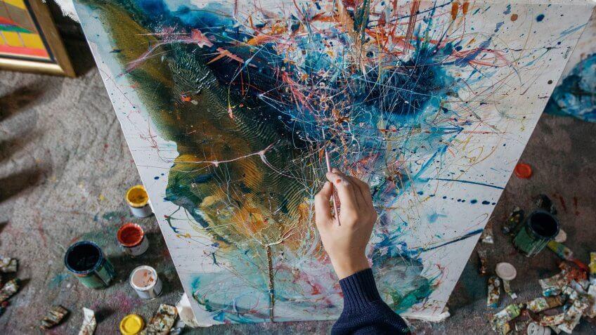 Artist- painter working on painting in studio with art supplies around him.