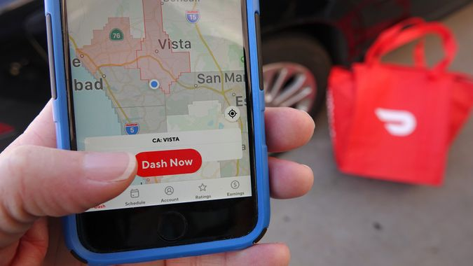 Close up of person logging into the DoorDash dasher app to begin delivering.