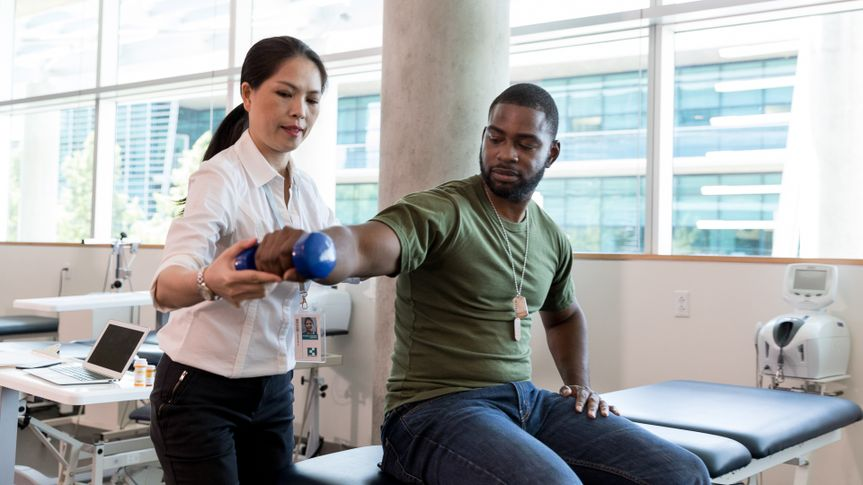 Serious army soldier with injury uses a hand weight during a physical therapy session.