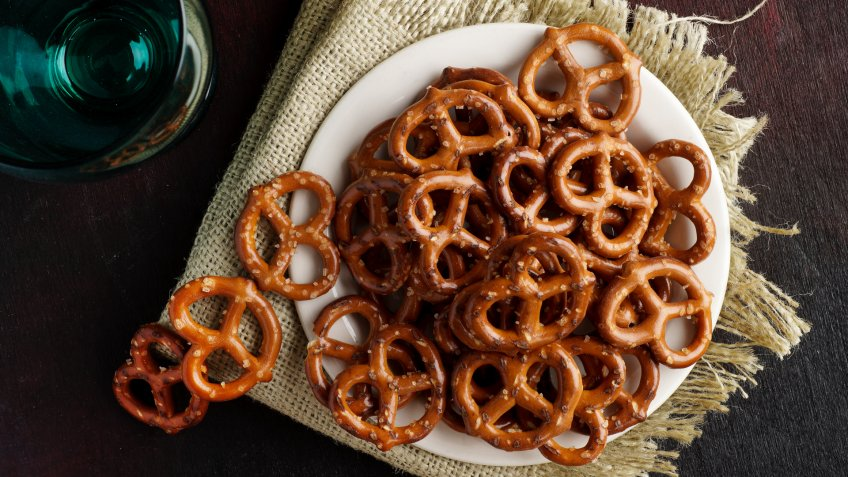 Macro photograph of pretzels on white plate on dark red black background.