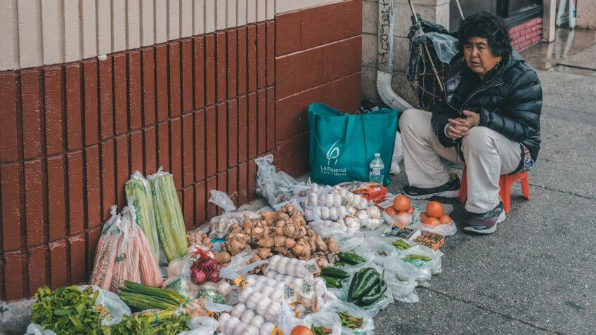 Los Angeles, CA, USA - April 5, 2018: Female street vendor sits along Broadway in Chinatown and sells small amounts of several vegetables and fruits displayed on the surface of the sidewalk.