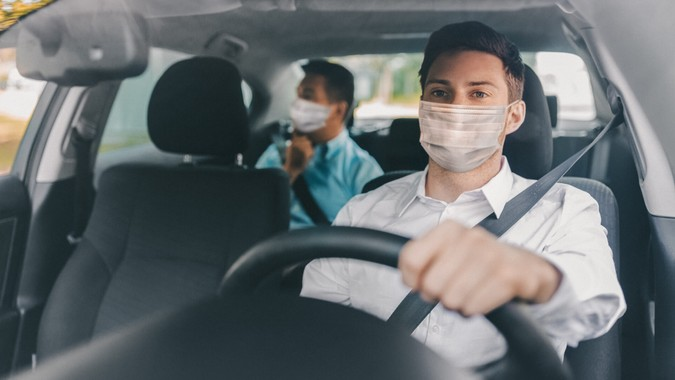 health protection, safety and pandemic concept - male taxi driver wearing face protective medical mask driving car with passenger.
