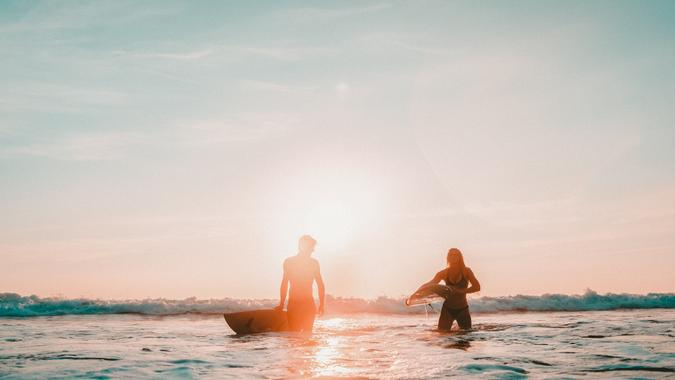 Couple returning after a long day surfing.